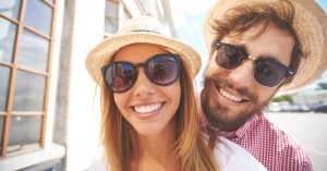 young white couple smiling & wearing sunglasses